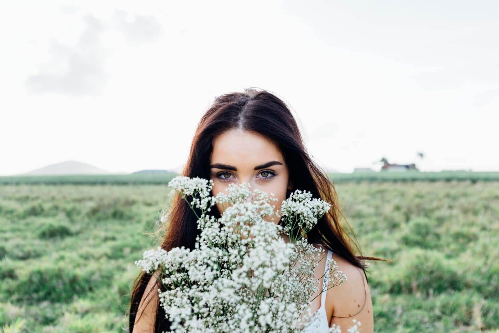 Kvinde med langt mørkt hår, skjuler noget af sit ansigt bag en buket blomster.