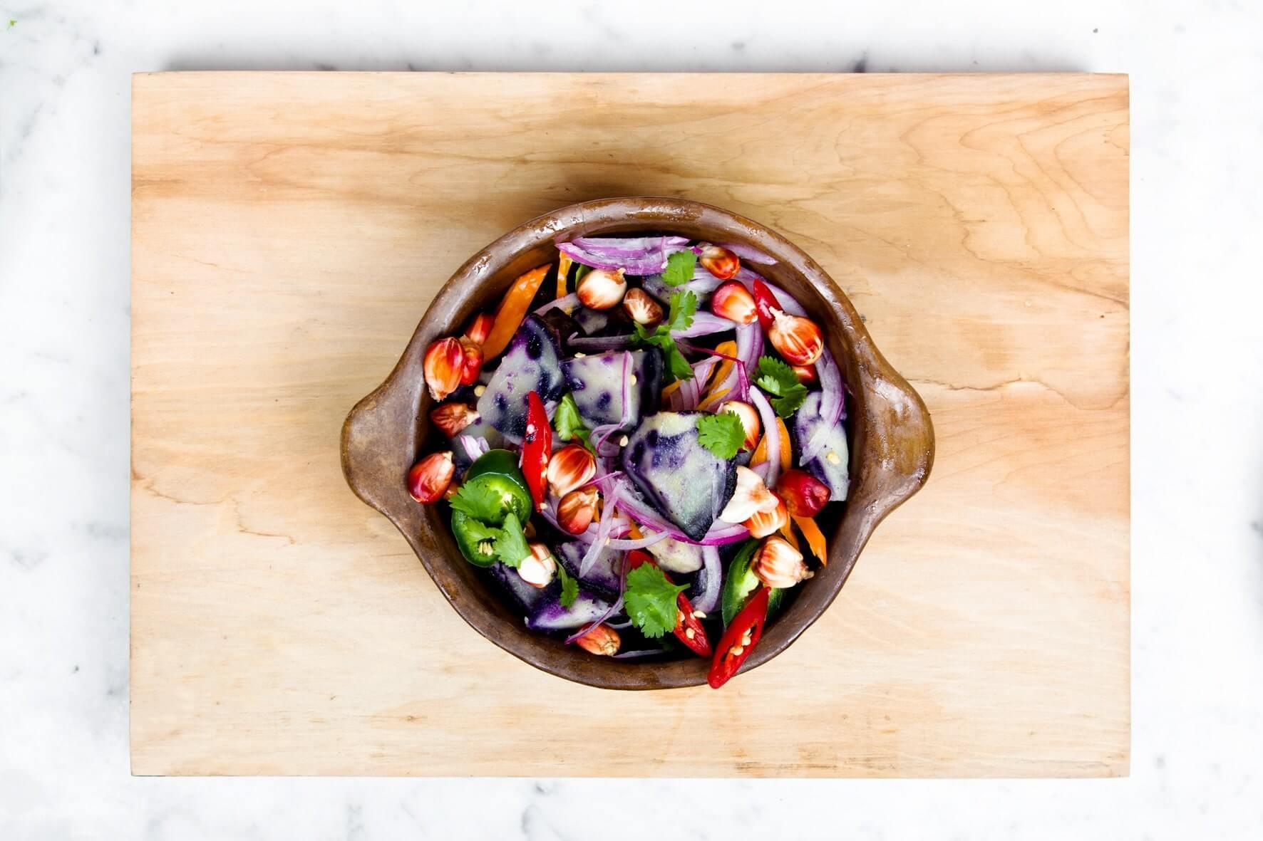Brun lerskål med forskellige, skårede grøntsager og krydreurter.