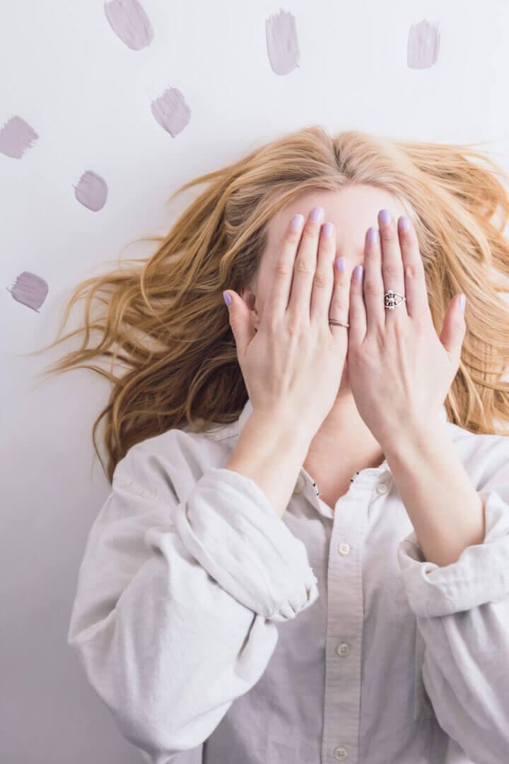 Kvinde med lysthår skjuler hendes ansigt med hendes håndflader.