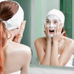 Ung rødhåret kvinde med hvid creme i hele ansigtet