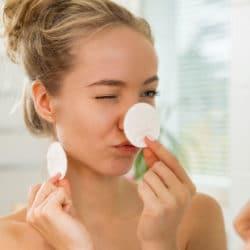 Ung kvinde blinker med øjet mens hun skjuler sin næse med en hvid vatrondel