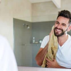 Ung smilende mand med nyvasket ansigt, tørre ansigtet med et blødt håndklæde.