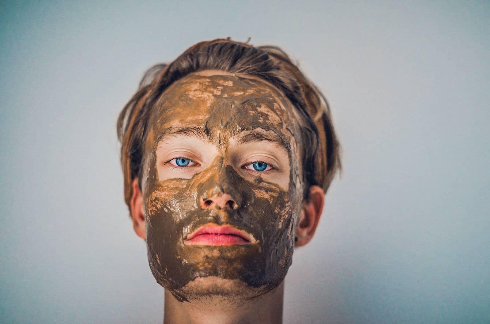 Mand med blå øjne og lyst hår, med ansigtsmaske eller muddermaske. AHA eller BHA