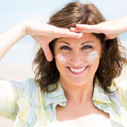 Kvinde med smilerynker ved øjnene har creme på kinderne