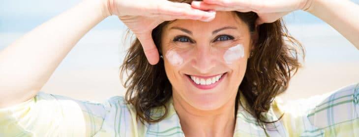 Kvinde med smile rynker ved øjnene har creme på kinderne