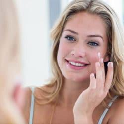 Ung smilende kvinde smøre creme på sin kind med sine fingre