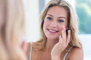 Ung smilende kvinde smøre creme på sart hud med sine fingre